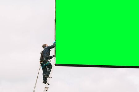 Industrial climber going up the ladder to the billboard. Risky job. Work on height. Freу space. Chromakey