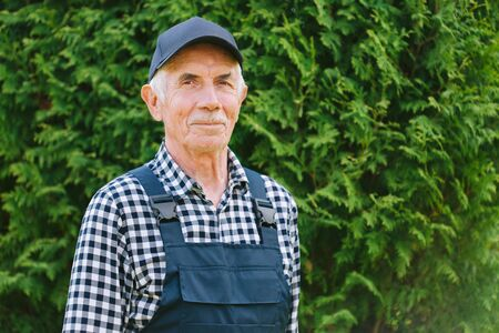 Senior professional worker in overall and cap. Aged farmer. Old craftsman. Foto de archivo