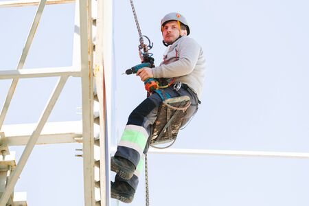 Industrial climber in helmet and overall working on height. Risky job. Professional worker 版權商用圖片 - 147905317
