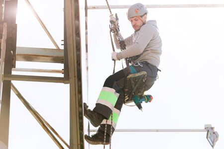 Industrial climber in helmet and overall working on height. Risky job. Professional worker 版權商用圖片