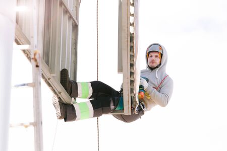 Industrial climber in helmet and overall working on height. Risky job. Professional worker 版權商用圖片 - 147905342