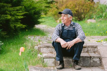 Senior gardener sitting on the steps in garden. Aged worker in overall and baseball cap resting after work. Portrait of old farmer