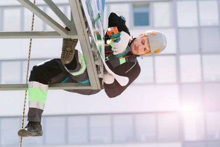 Industrial climber in helmet and overall working on height. Risky job. Professional worker Foto de archivo