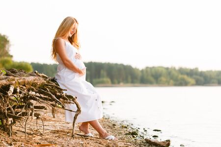 Pregnant blonde woman in long white dress on the beach. Future mother with belly