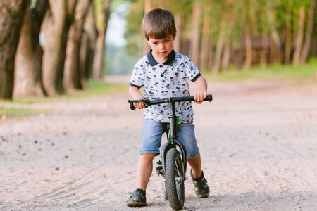 Cute little boy on balance bike. Kid on bicycle. Preschooler learning to balance on run bicycle. Sport for kids