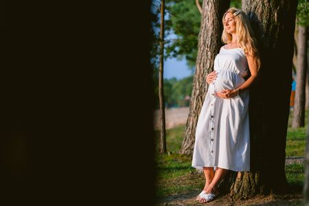 Pregnant blonde woman in long white dress in the forest. Future mother with belly. Pregnancy, family, preparation and expectation concepts.