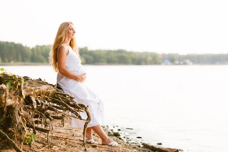 Pregnant blonde woman in long white dress on the beach. Future mother with belly 版權商用圖片 - 149095551