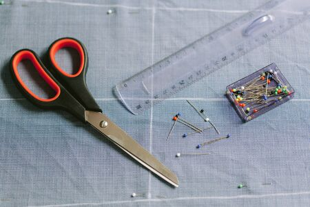 Tailor's work table. Close up. Ruler scissors chalk needles pins Foto de archivo