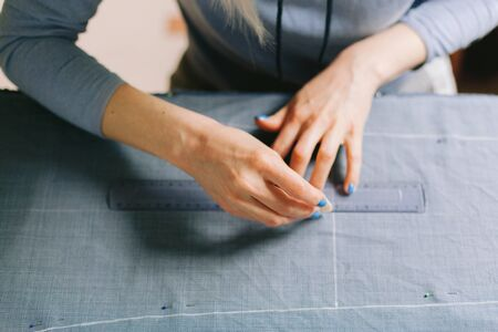 Close up. Tailor marking out the pattern of the garment she is making with tailors chalk. Working at home 版權商用圖片