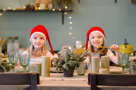 Two Happy cheerful Little girls in santa hat sitting at the festive table. Christmas time. Sisters having fun