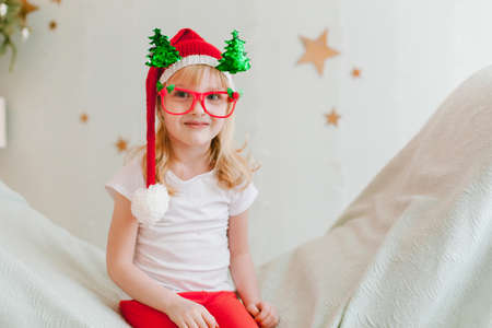 Happy cheerful Little girl in santa hat. Christmas time