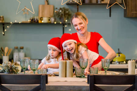 Mother with Two Happy cheerful Little girls in santa hat sitting at the festive table. Christmas time. Woman having fun with daughters 版權商用圖片 - 160159615