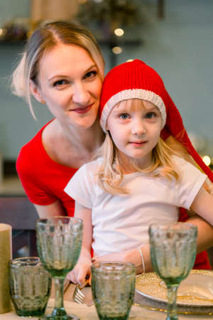 Mother with Happy cheerful Little girl in santa hat sitting at the festive table. Christmas time. Woman having fun with daughter