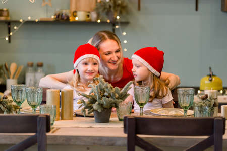 Mother with Two Happy cheerful Little girls in santa hat sitting at the festive table. Christmas time. Woman having fun with daughters