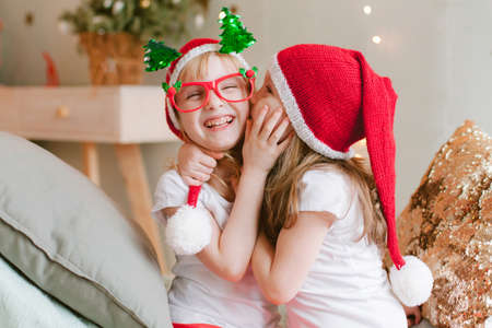 Two Happy cheerful Little girls in santa hat. Christmas time. Sisters having fun