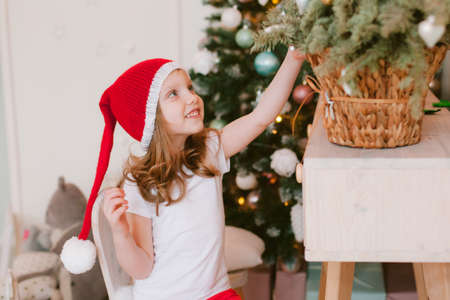 Happy cheerful Little girl in santa hat. Christmas time.