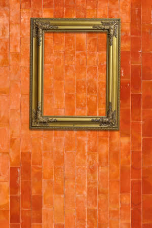 Gold picture frame on grunge orange brick wall photo
