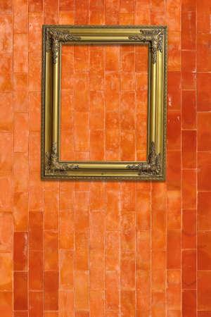 Gold picture frame on grunge orange brick wall Stock Photo - 13166588