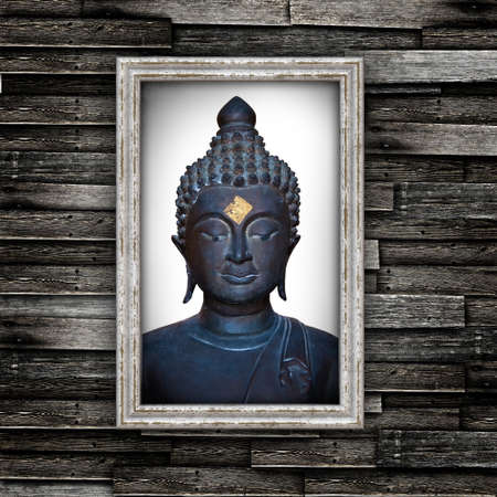 Head of Buddha in grunge frame on wooden wall