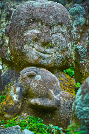 followers: STONE STATUE � SMILEY FACE: A Buddha�s disciple statue carved in stone with smiling facial expression. It is eroded through time and covered in moss. Stock Photo
