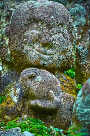STONE STATUE - SMILEY FACE: Buddhova žák socha vytesaná do kamene s úsměvem výrazu obličeje. Je časem erodovaný a pokrytý mechem.