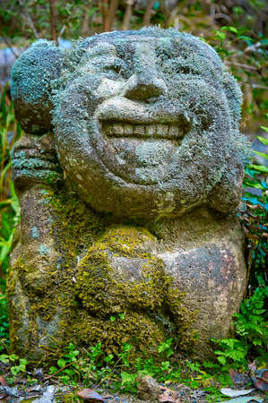 STONE STATUE - HAPPY FACE : A Statue sculpted in stone with smiling face. It is old and eroded through time. The whole statue is covered in moss and tiny leaves.