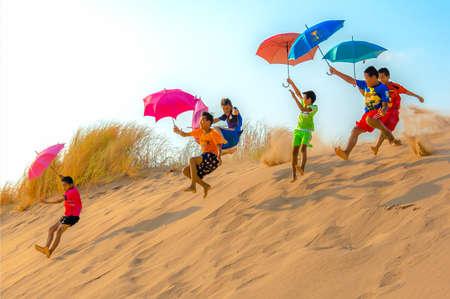 KIDS PARACHUTING SAND DUNES mit Sonnenschirmen: Kinder haben Spaß. Sie rennen miteinander auf die Spitze der Sanddüne und springen von der Kante, indem sie Regenschirme als Fallschirme benutzen, um sie die Dünen hinab zu gleiten.
