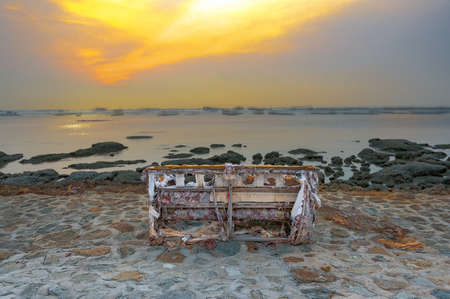 withering: SOFA ON THE SHORE : A ragged sofa with torn and worn out upholstery is left abandoned on the shore, slowly withering away by the heat of the sun. Stock Photo