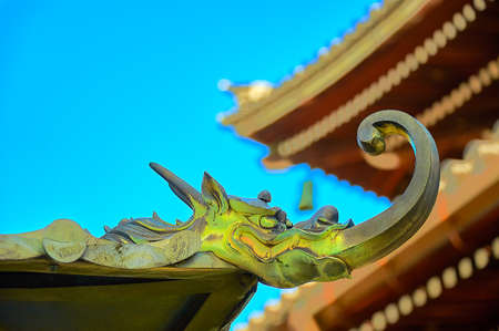 Dragon sculpture on temple ridge : The mystical roof guardian figure sets on the temple ridge to watch mankind to behavior and faithfulness.