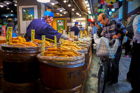 Nishiki Market, Kyoto, Japan  – October 22, 2016 : Old man came with his bicycle stood in front of a store which sells variety of pickled food. He is asking for one of them to the vendor.