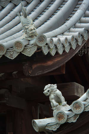Mystical lion sculptures on the roof: The mystical roof guardians set to watch over men and women behaviour and faithfulness. Commonly used as part of ancient Japanese and Chinese architectures. Stock Photo
