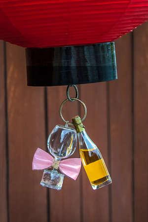 Nature morte - bouteille de vin et verre de vin. Une bouteille de vin, et un verre de vin avec n?ud papillon rose attaché sont accrochés au fond de l'abat-jour en papier rouge. Banque d'images - 87069983