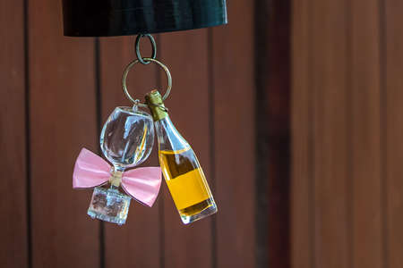 lamp shade: Still life - bottle of wine and wine glass. A bottle of wine, and a wine glass with pink bow tie attached are hung to the bottom of red paper lampshade.