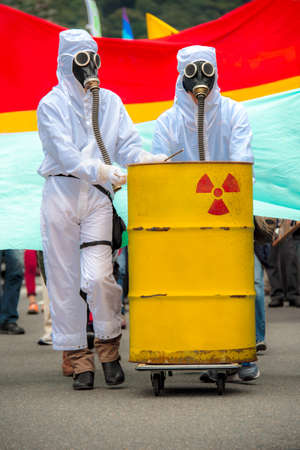 Two men in bio-hazard suit and gas mask. Two men in bio-hazard suits standing behind a rusty tank with nuclear symbol screened on. They are wearing a gas masks with flexible rubber breathing tubes.