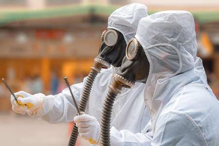 バイオ ハザード スーツとガスマスクで二人の男。彼らの両方は呼吸管柔軟なゴム製のガスマスクを着用します。それらの 1 つは錆びた鉄筋のペアを保持します。 写真素材 - 87392498