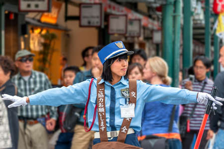 light duty: Friendly traffic warden on duty. Gion district, Kyoto, Japan – October 23, 2016: Between 'Hanamikoji Dori' and Shijo Dori junction, a female traffic warden extends her arms to stop crowd wanting to cross the street while letting cars going throu Editorial