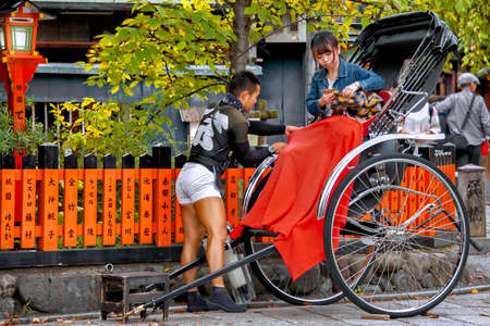 Rickshaw Taxi Ride. Gion Shirakawa Street, Kyoto, Japan – October 23, 2016: Rickshaw driver secures a red blanket to his customer as she is settling down for her journey.