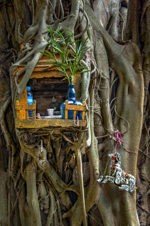 SPIRIT HOUSE AND TREE ROOTS INTERTWINED. Miniature house for guardian spirit. A dedicated structure to honour the guardians of the land that is found in the Southeast Asian countries of Burma, Cambodia, Laos, and Thailand. Фото со стока - 88874771