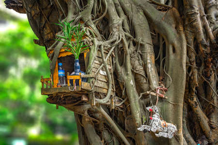 SPIRIT HOUSE AND TREE ROOTS INTERTWINED. Miniature house for guardian spirit. A dedicated structure to honour the guardians of the land that is found in the Southeast Asian countries of Burma, Cambodia, Laos, and Thailand.