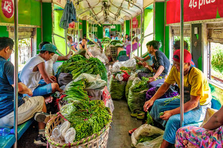 Yangon Circular Railway, Myanmar - Oct. 22, 2017: Local railway line utilized mainly by low-income commuters, vendors, sellers, greengrocers. Some board the train with vegetables in large plastic sacks and rattan baskets to cut and trim them on board. 에디토리얼