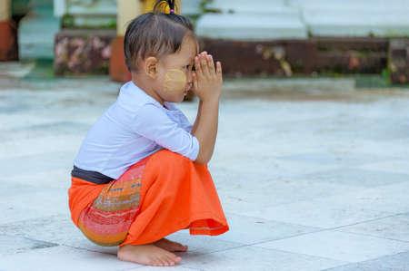 Shwedagon Pagoda, Yangon, Myanmar - Oct 21, 2017: A little Burmese boy kneels down as he clasps his palms and prays to the Lord Buddha. Editorial