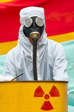 A man in bio-hazard suit and gas mask. A man in bio-hazard suit standing behind a rusty tank with nuclear symbol screened on. He is wearing a gas mask with flexible rubber breathing tube.