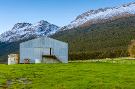 Queenstown, NZ- April 14, 2018: A barn on a grassland built in the natural setting where mountains and hills are nearby, with a flock of sheep grazing in the area.