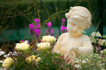 LITTLE ANGEL IN A FLOWER GARDEN. Sculpture of a cute little angel in a garden with assortment of flower varieties. Archivio Fotografico
