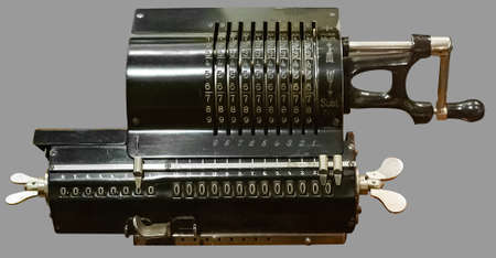 ANTIQUE ROTARY CALCULATOR. Old vintage rotary calculator on isolated grey background with clipping path.