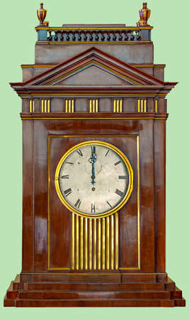 Antique clock in wooden box in classical Roman architecture, on isolated green background with clipping path.