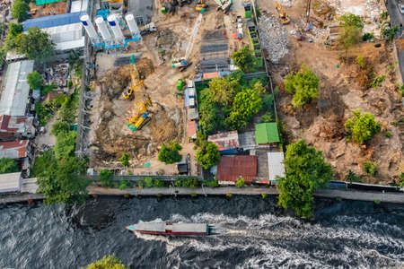 Aerial view of a water bus on a canal in Bangkok, and a construction site along the embankment with heavy equipment preparing for foundation work. 版權商用圖片