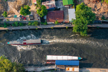 Aerial view of a water bus on a canal in Bangkok, and a construction site along the embankment preparing for foundation work. Stock Photo