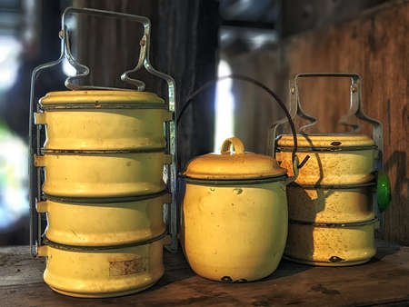 Staged lunch box, commonly used in Asian countries. Old and rustic tiffin carriers and a yellow pot, taken with shallow depth of field. Stock fotó