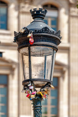 Bundle of padlocks and a red heart keyring locked onto a lamppost at 'Pont des Arts' pedestrian bridge in Paris.